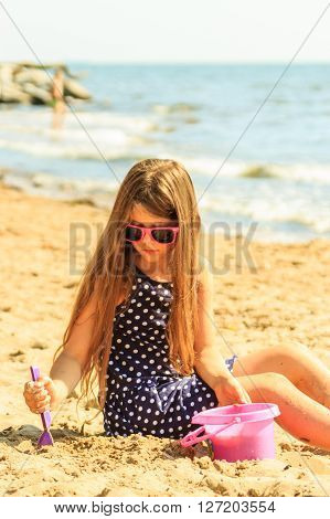 Little girl child with toy having fun on beach. Kid with shovel digging hole in sand. Summer vacation holidays relax.