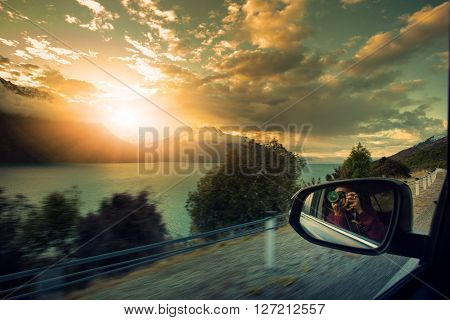 photographer taking a photo of sun set sky on the way to destination