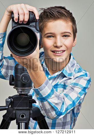 Boy with photo camera on thripod posing at studio
