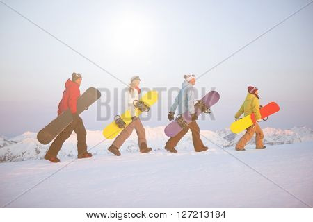Group of snowboarders on top of the mountain.