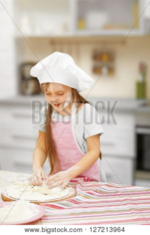 Beautiful little girl cutting hearts from a dough