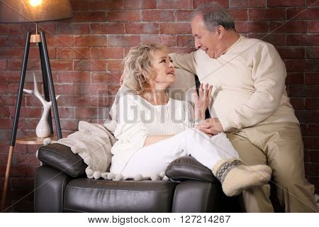Mature couple sitting together on a armchair at home