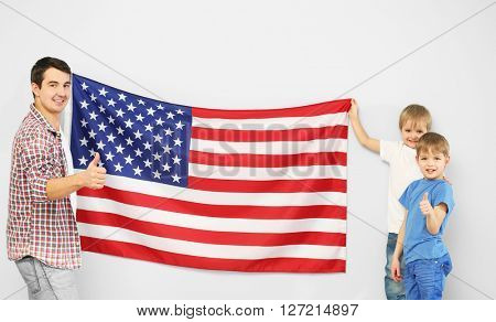 Father and his sons holding    USA flag on the light blue wall
