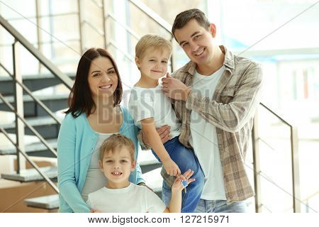 Happy family with key in new house on stairs background