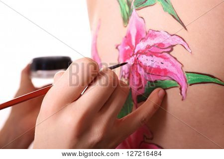Hand with brush painting pink lily on a female back