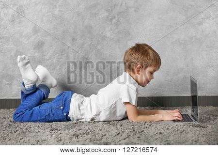 Little boy using laptop on fur carpet against grey wall background