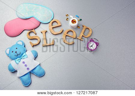 Word Sleep with pills, sleeping mask and little toy  on a grey background