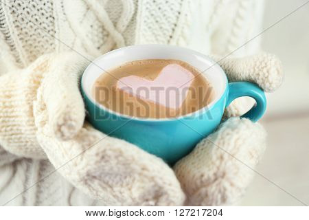 Female hands in warm mittens holding cup of hot cappuccino with heart marshmallow, close up
