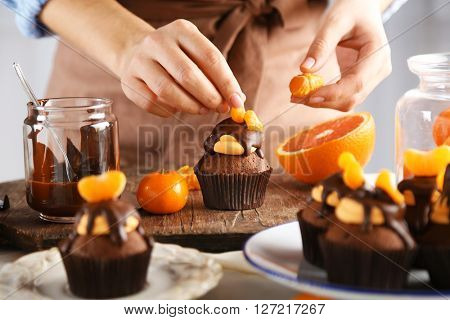 Female baker decorating tasty cupcake with slice of mandarin and chocolate on the table