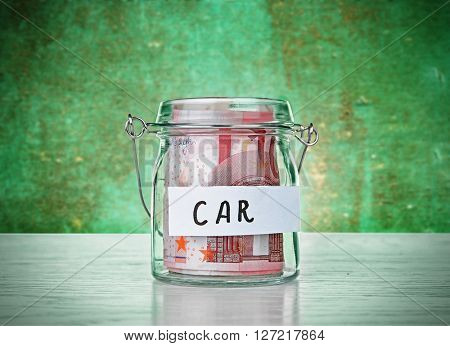 Jar for savings full of coins on wooden background