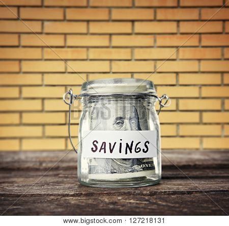 Jar for savings full of coins on wall background