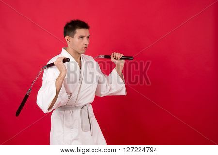 fighter in white kimono with nunchaku training on a red background