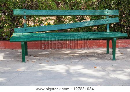 Badly fixed bench made with gree wood panels