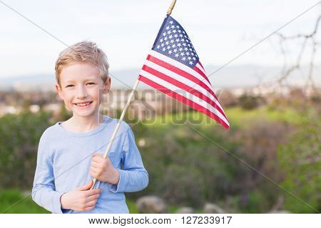 positive smiling boy holding american flag and celebrating 4th of july