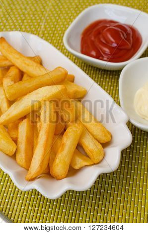 French fries in a white bowl with tomato sauce and mayonnaise