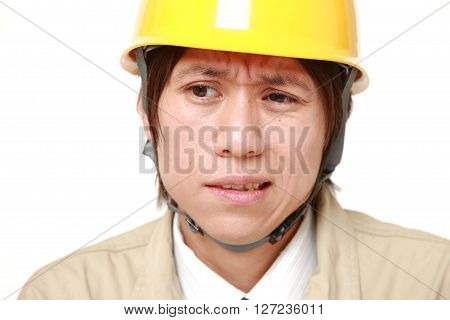 perplexed young Japanese construction worker on white background