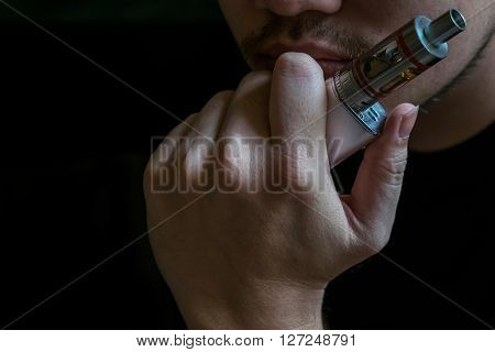 Man with concealed identity smoking a controversial vaping an electronic cigarette. Vaping is debatable in the health community if it is safe or a health risk