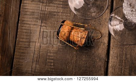 Cork of a champagne bottle against two champagne flutes
