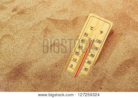 Thermometer with celsius and farenheit scale on warm beach sand showing record extreme high temperatures