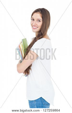 Side view of smiling female college student holding books while standing on white background