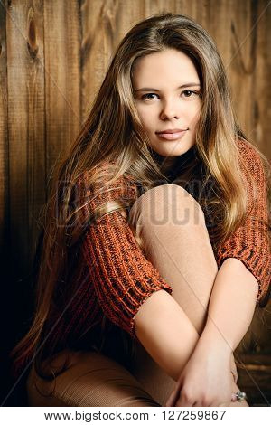 Pretty teenager girl in casual clothes sitting by a wooden wall. Modern teen generation. Youth fashion. Healthy hair, haircare.