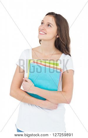 Smiling female college student holding books while standing on white background