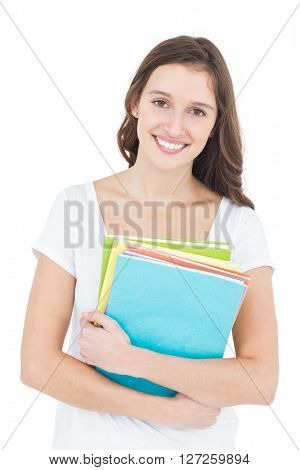 Portrait of cheerful female college student holding books while standing on white background