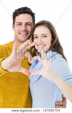 Happy couple showing a heart shape with their fingers on white background
