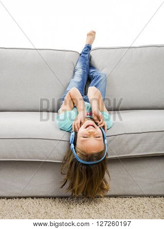 Little blonde girl at home listen music with headphones