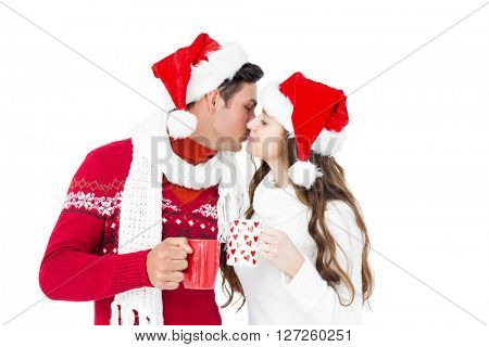 Happy couple with santa hats holding mug and kissing on white background