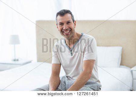 Portrait of man sitting on bed and smiling in bedroom