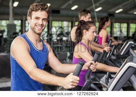 Fit people on elliptical bike at gym