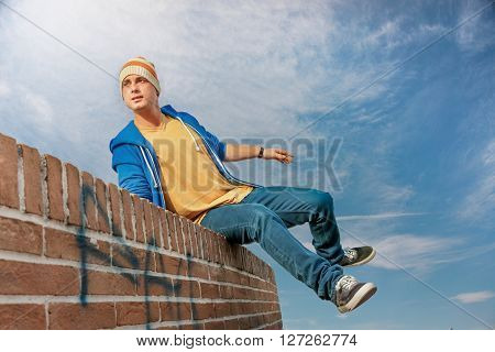 young athletic man doing parkour on rooftop wall running and jumping action in urban style with blue sky background