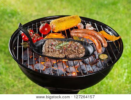 Assorted delicious grilled meat with vegetable on a barbecue grill.