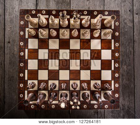 Chess pieces on old wooden table. Top view.