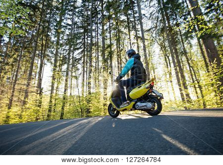 Man riding scooter on forest road. Spring season.
