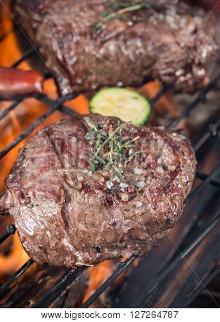 Delicious grilled beef steaks on a barbecue grill, close-up.