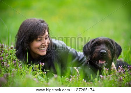 Beautiful Brunette woman with black dog posing on spring meadow.