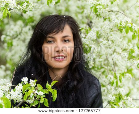Beautiful young brunette woman standing near the apple tree. Portrait photo.