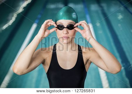 Woman in swimsuit adjusting her goggles at the pool