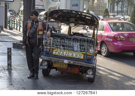 BANGKOK THAILAND - APR 10 : tuktuk is parking on sidewalk of siam square on april 10 2016 thailand. Tuktuk is name of three wheeled taxi car in thailand