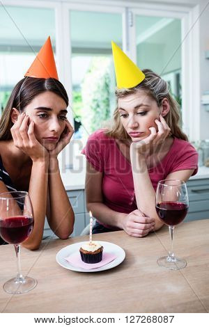 Sad friends with hand on chin while sitting at table during birthday party at home