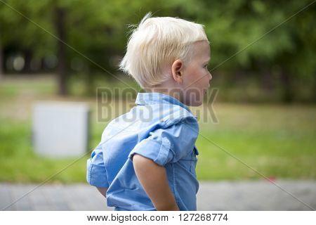 Portrait of blonde baby boy in blue shirt on summer street city