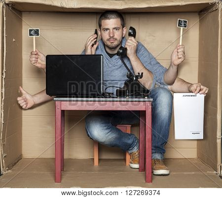 Young Man In The Office Box Is A Very Multitasking