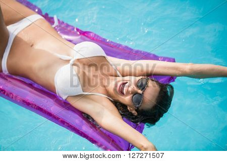 Cheerful young woman swimming with inflatable raft at pool