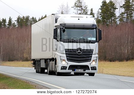 SALO, FINLAND - APRIL 22, 2016: White Mercedes-Benz Actros Semi Truck trucking along rural road in South of Finland on a cloudy day.