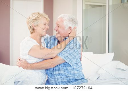 Happy senior couple embracing in bedroom at home