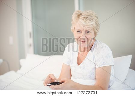 Portrait of senior woman using phone on bed at home