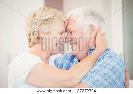Close-up of happy senior couple embracing in bedroom at home