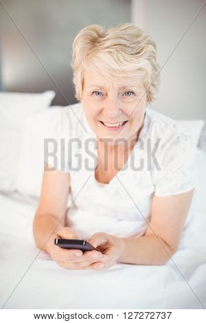 Portrait of smiling senior woman using phone on bed at home